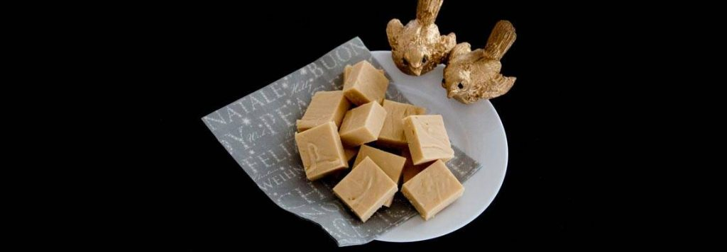 Plate of Baileys and White Chocolate Fudge sitting on a christmas napkin with 2 gold bird ornaments