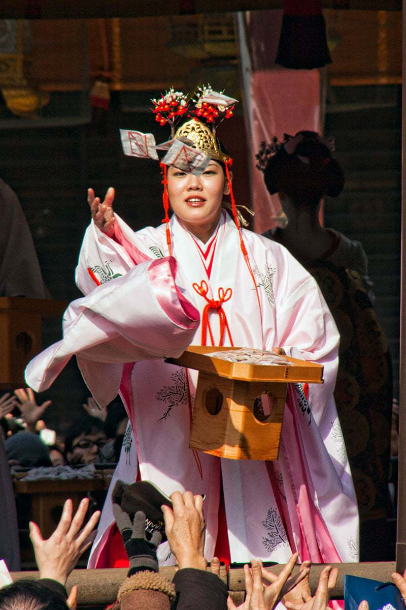 Setsubun is one of the most fun celebrations on the Japanese calendar. A Miko (with a maiko behind) at Yasaka Shrine throws lucky soy beans to the crowd