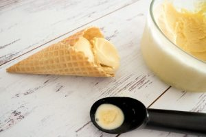 Baileys Ice Cream in a bowl, sugar cones and scoop on light background