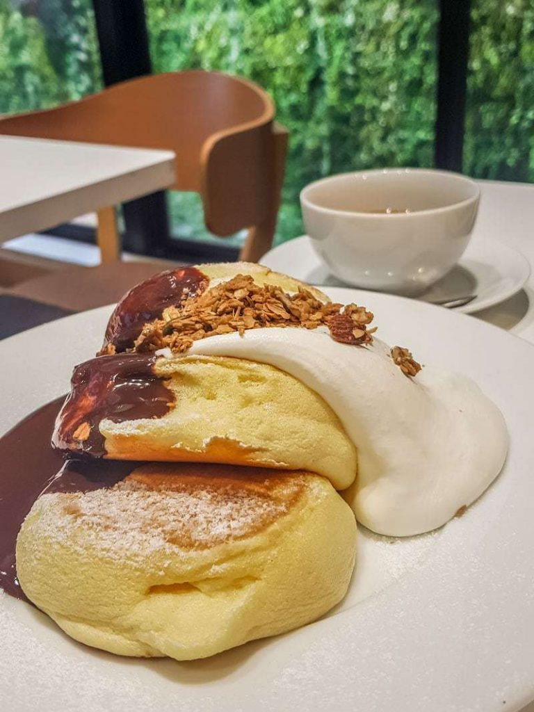 Souffle pancakes with chocolate sauce, granola and cream with backdrop of vines outside the window at A Happy Pancake in Shibuya, Tokyo