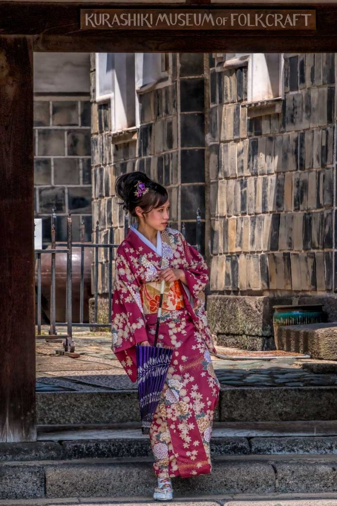 Girl in kimono exits the Kurashiki  museum of folkcraft