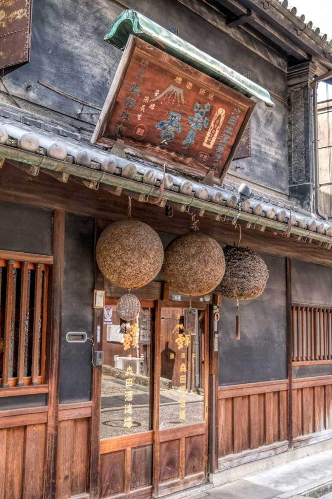The front of traditional wooden building used by Morita sake brewery in Kurashiki with the 3 cedar balls in the doorway