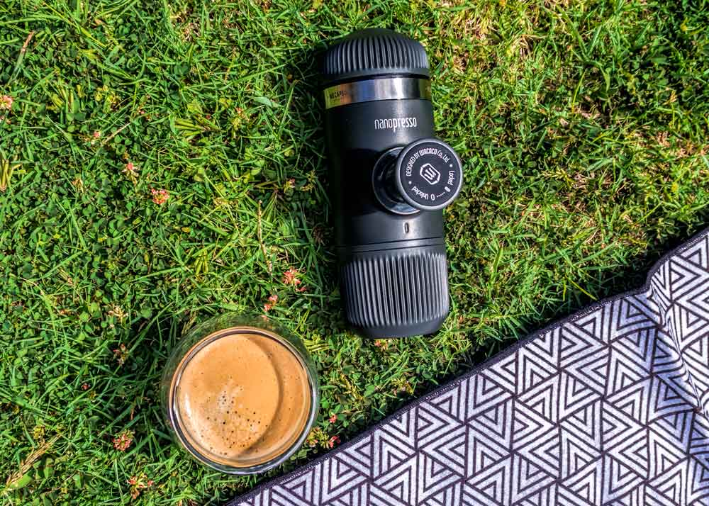 Nanopresso coffee press on grass with cup of coffee and picnic blanket