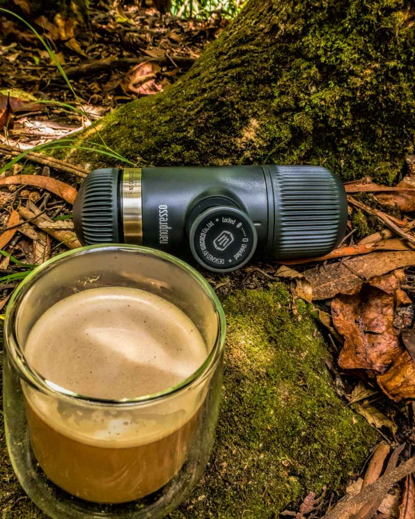 Nanopresso coffee press sitting on mossy rock with fallen forest leaves behind