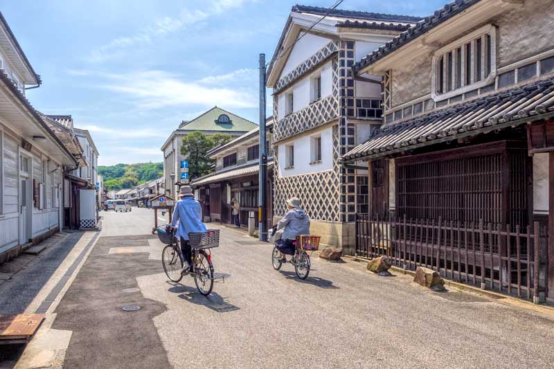 A traditional street in Kurashiki Bikan with local cyclists passing one of the old whte walled rice storehouses