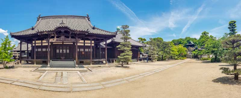 A panorama photo of the Honeiji temple courtyard and temple buildings in Kurashiki Japan