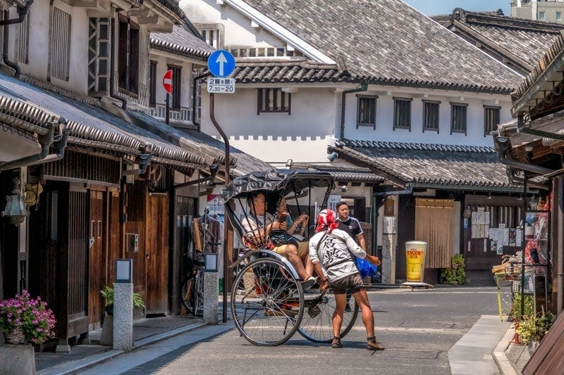 A rickshaw is pulled by hand through the heritage streets of Kurashiki