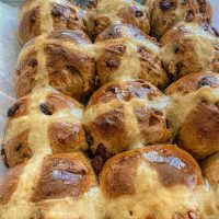 tray of glazed hot cross buns direct from the oven