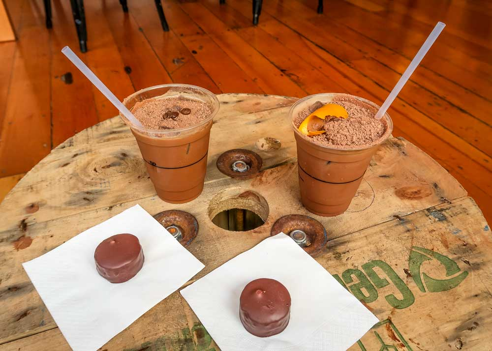 Iced chocolate and handmade chocolate on wooden cable roll cafe table